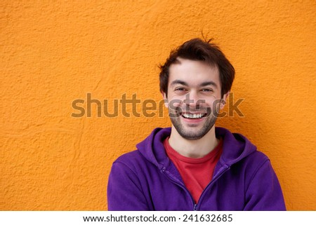 Close up portrait of a cheerful young man smiling on orange background - stock photo