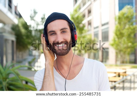 Close up portrait of a cheerful young man with headphones outdoors - stock photo