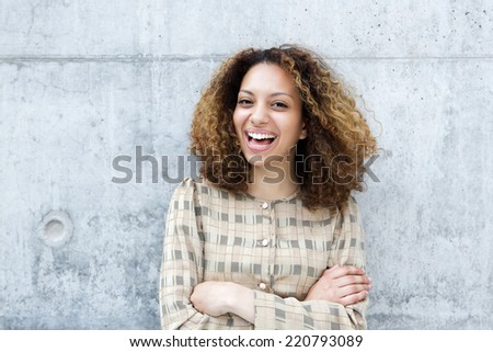 Close up portrait of a cheerful young woman laughing outdoors with arms crossed - stock photo
