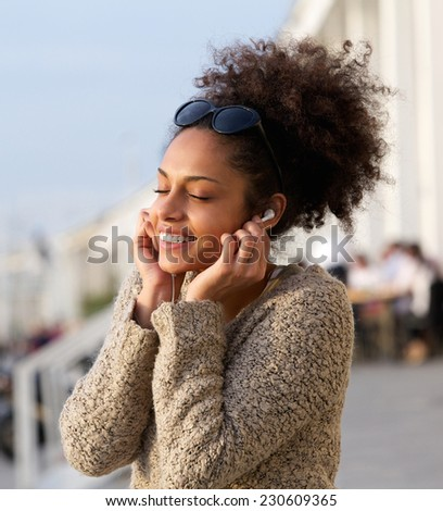 Close up portrait of a cheerful young woman listening to music outdoors - stock photo