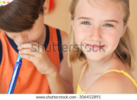 Close up portrait of a child girl turning and smiling at the camera while enjoying a summer holiday with her friend who is blowing a party blower, home exterior. Kids having fun outdoors. - stock photo
