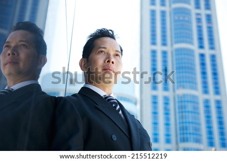 Close up portrait of a confident asian businessman standing in the city - stock photo