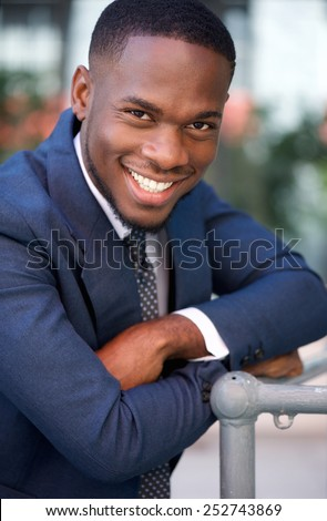 Close up portrait of a confident businessman smiling with arms crossed