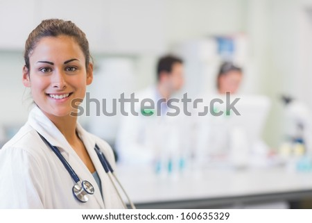 Close-up portrait of a confident female doctor with colleagues in background at medical office - stock photo