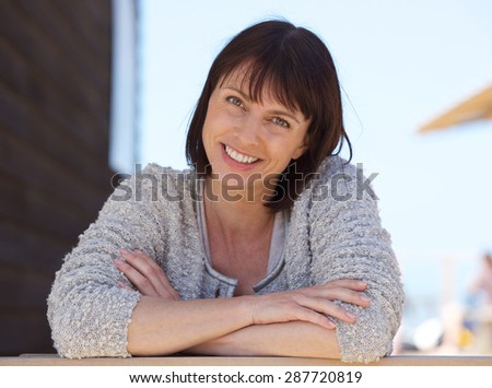 Close up portrait of a confident middle aged woman smiling outside - stock photo
