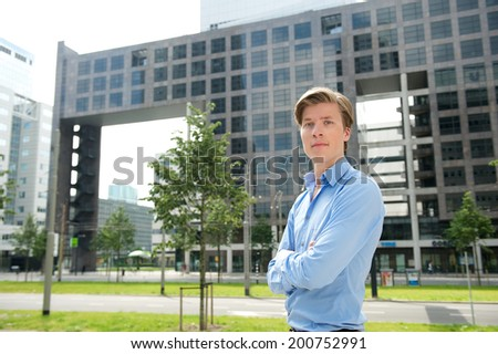 Close up portrait of a confident young businessman posing with arms crossed