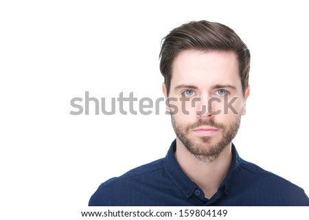 Close up portrait of a confident young man with beard looking at camera - stock photo