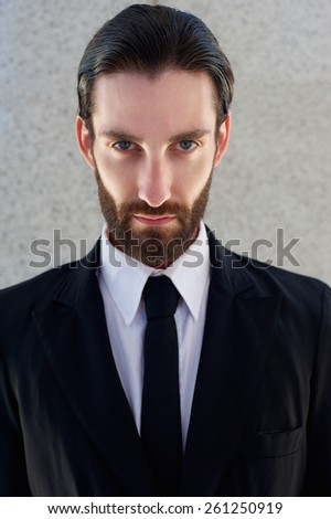 Close up portrait of a cool male fashion model with beard posing in black suit and tie - stock photo