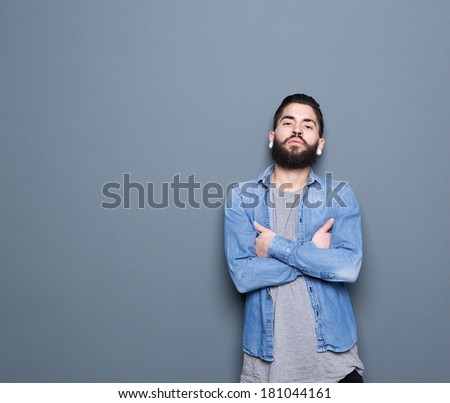 Close up portrait of a cool young guy posing on gray background with arms crossed