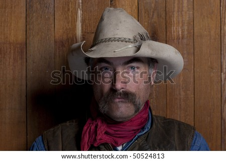 Close-up portrait of a cowboy with a mustache in front of a rough wood wall. He is staring at the camera with a serious expression. Horizontal format. - stock photo