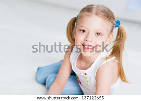 close-up portrait of a cute girl, lying on the floor in the living room - stock photo