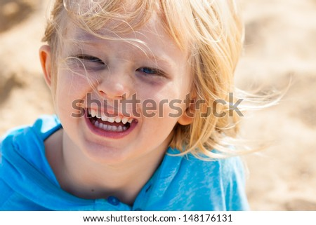 Close-up portrait of a cute laughing boy playing  outdoors - stock photo