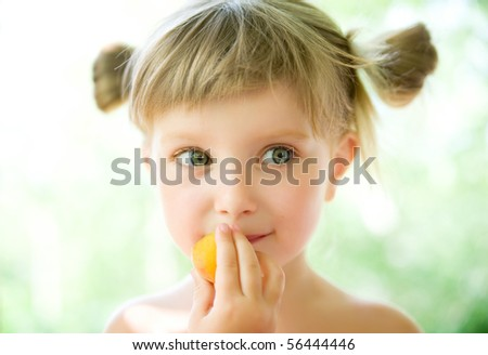 Close-up portrait of a cute liitle girl with the apricot - stock photo