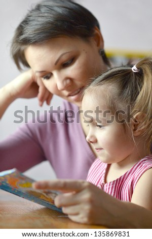 close-up portrait of a cute little girl and her mother reading a book