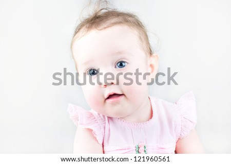Close up portrait of a cute little girl in a pink dress
