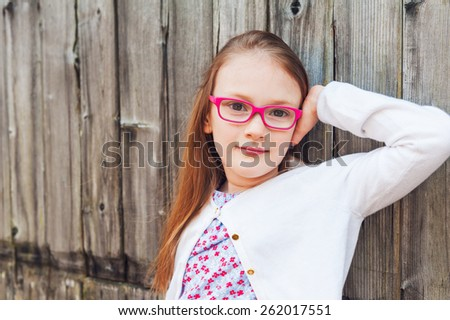 Close up portrait of a cute little girl of 7 years old, wearing pink eyeglasses, standing against wooden background - stock photo