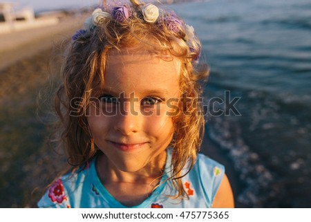 close up portrait of a cute smiling child girl in blue dress and flower wreath