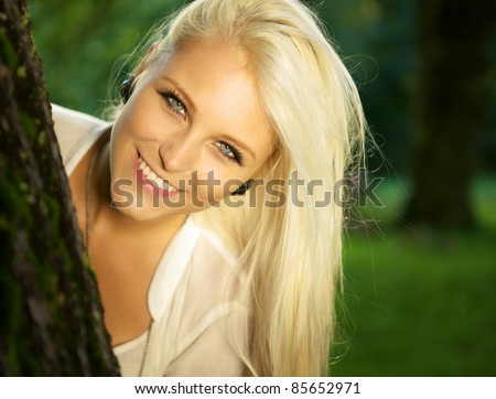 Close-up portrait of a cute smiling female in a forest. - stock photo