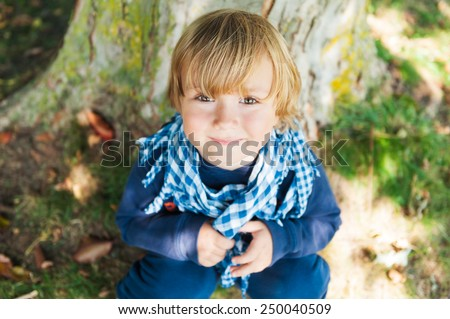 Close up portrait of a cute toddler boy resting under the tree on a nice sunny day - stock photo
