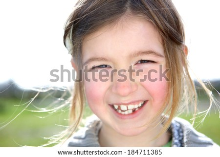 Close up portrait of a cute young girl laughing outdoors  - stock photo