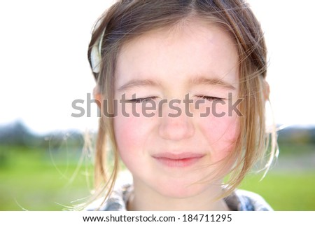Close up portrait of a cute young girl with eyes closed thinking or imagining  - stock photo