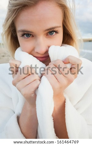 Close up portrait of a cute young woman in stylish white jacket on the beach