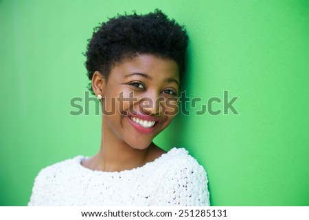 Close up portrait of a cute young woman smiling on green background - stock photo
