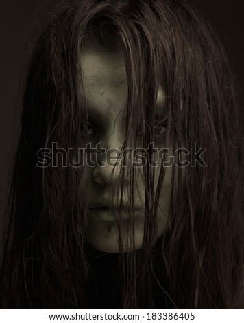 Close up portrait of a demon. Zombie make up, spooky, ugly horror girl - stock photo