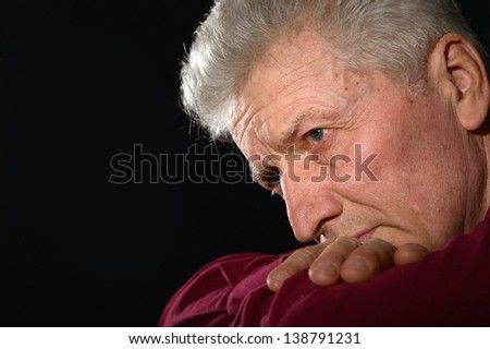 close-up portrait of a depressed elderly man on a black background