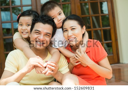 Close-up portrait of a family smiling and looking at camera - stock photo