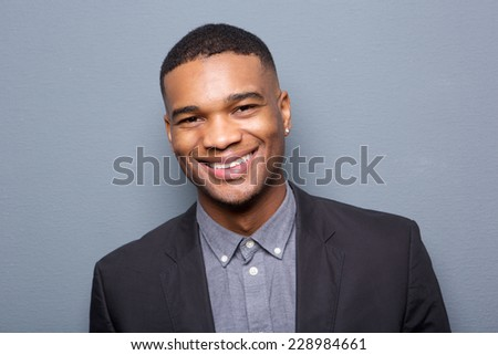 Close up portrait of a fashionable black man smiling on gray background - stock photo