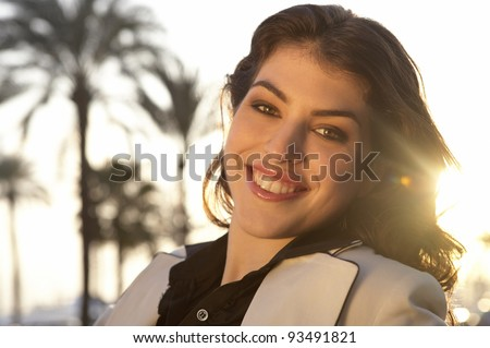 Close up portrait of a fashionable woman sitting outdoors, with sun rays filtering from the back. - stock photo