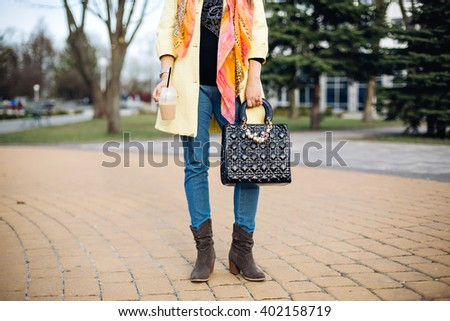 close-up portrait of a fashionable young lady posing in the city, accessories, spring shoes,perfect feet, the spring collection of boots,stylish gray ankle boots, fashionable yellow coat,black bag - stock photo