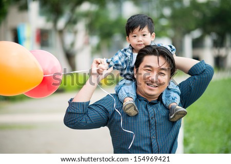 Close-up portrait of a father carrying his son on the shoulders with colorful balloons  - stock photo
