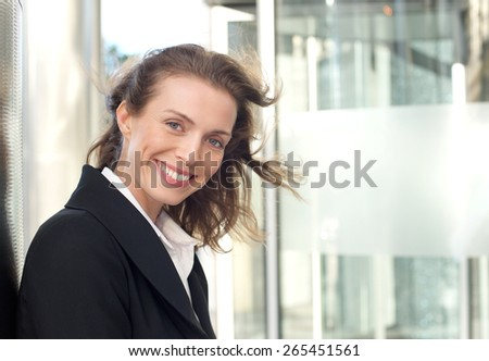 Close up portrait of a friendly business woman smiling outside - stock photo