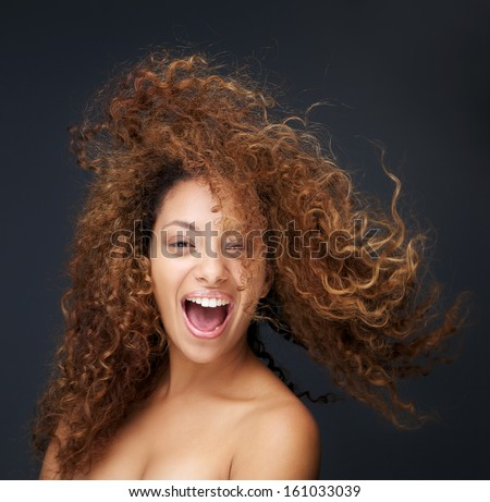 Close up portrait of a fun and happy young woman laughing with hair blowing - stock photo