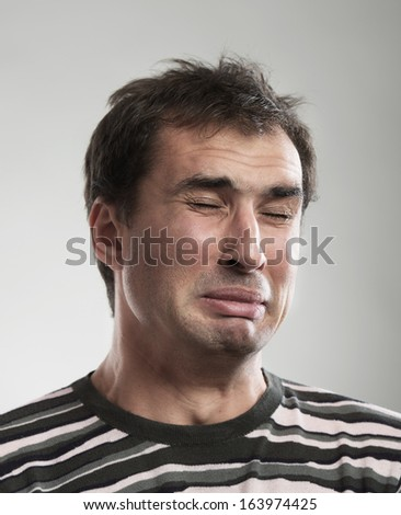 Close-up portrait of a funny crying man - stock photo