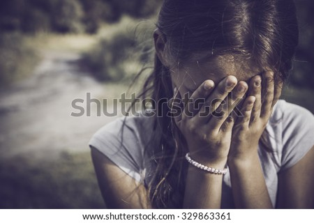 close-up portrait of a girl crying and covering her face - stock photo