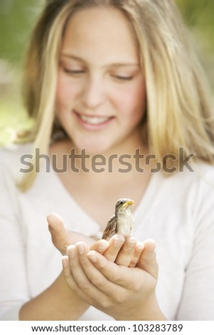 Close up portrait of a girl in the garden, holding a bird in her hands and smiling. - stock photo