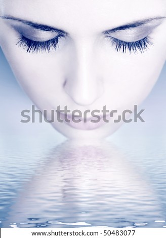 Close-up portrait of a girl washing her face - stock photo