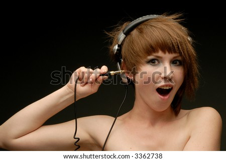Close up portrait of a girl with earphones on sticking patch tip into her ear - stock photo