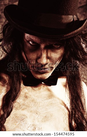 Close-up portrait of a gloomy vampire standing at the night background. Halloween. - stock photo