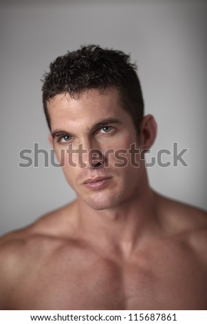 close up portrait of a good looking man with his shirt of looking at camera - stock photo