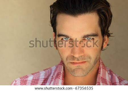 Close up portrait of a good looking masculine young man against neutral background with lots of copy space - stock photo