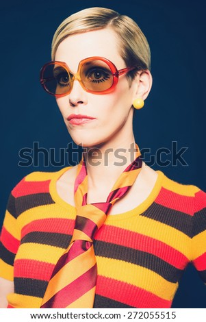 Close up Portrait of a Gorgeous Blond Woman in Trendy Fashion, Wearing Sunglasses, Striped Necktie and Shirt, Looking to the Left of the Frame on a Dark Blue Background. - stock photo