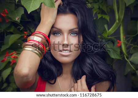 Close up portrait of a gorgeous brunette in red dress standing near the bush with red flowers - stock photo