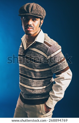 Close up Portrait of a Gorgeous Stylish Afro Guy, Wearing Long Sleeved Stripes Shirt and Cap, Staring to the Right on a Dark Blue Background. - stock photo