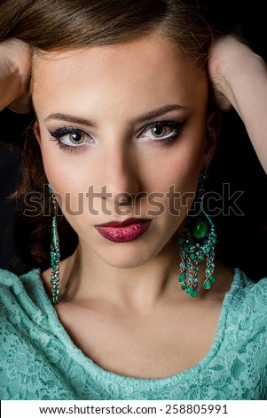 Close up Portrait of a Gorgeous Young Woman with Makeup Staring at the Camera with Both Hands on her Head on a Black Background. - stock photo