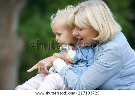 Close up portrait of a grandmother holding baby girl and pointing - stock photo