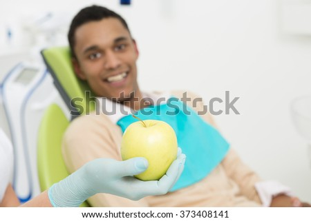 Close-up portrait of a green apple represented on the background of young man patient at the dentist's office. - stock photo